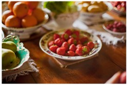 Summer Supper - Strawberries and other fruits laid out on the dining room table as part of Laura Mansfield's installation in 2013
