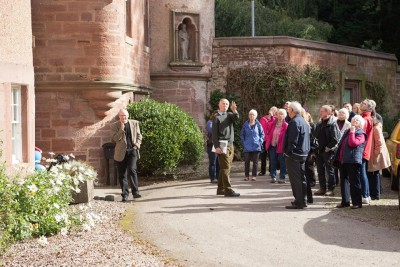 A tour group starting the introduction to the history of the site outside the red sandstone walls of Hospitalfield House on a bright day.