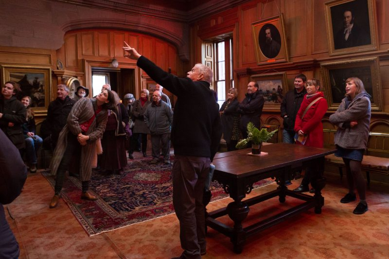 Volunteer tour guide Alec Edwards leading a tour in the panelled Cedar Room of Hospitafield House and gesturing up towards a portrait of the last owners.