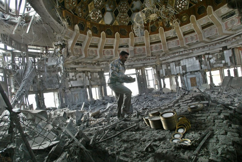 An Iraqis looter takes stacks of gold-adorned china from the bomb blasted dome of Saddam Hussein's Al-Salam Presidential Palace in Baghdad on Sunday, April 13, 2003.  Iraqi looters, taking advantage of the lawlessness of Baghdad after the city fall, turned their attention to the symbols of Saddam's Hussein's regime. (AP Photo/David Guttenfelder)