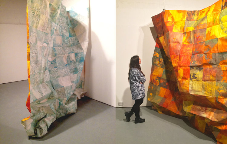 Two large printed surfaces creating an installation, with a figure standing between them in the gallery space. Created by Francine Kay Affourtit.