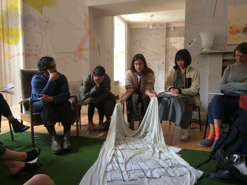 An artist shares their work in a circle of other artists in a room in Hospitalfield house.