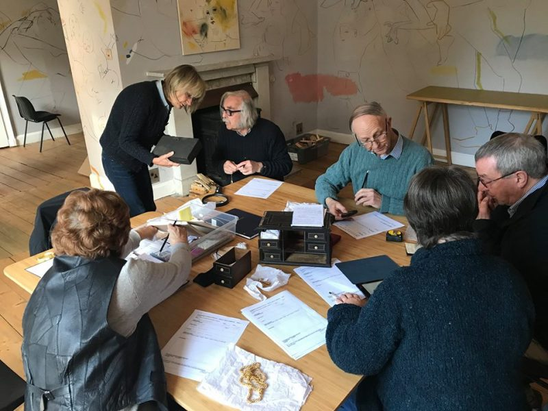 six people sit around a table looking at a series of papers. The walls of the room are painted all over by artist France-lise McGurn