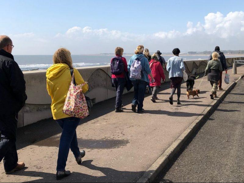 People walking along the Arbroath beach promenade