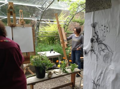 Person drawng on an easel in the greenhouse