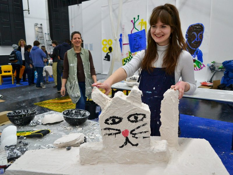 Artist Sally Hackett holding a clay cat in a workshop