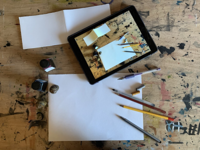 Paper pencils and an Ipad on a desk