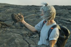 Artist Rachel Pimm holds up a volcanic rock and looks at it while standing on a desolate rocky landscape