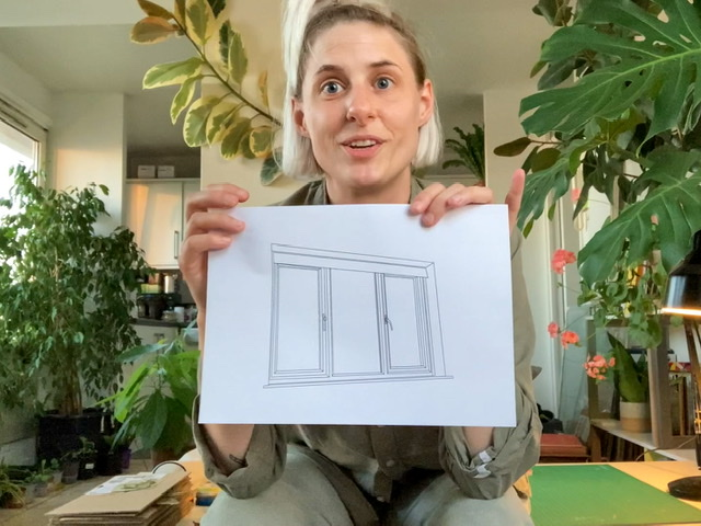 Artist Rachel Pimm holds up a piece of white paper with a digital drawing of a window on it