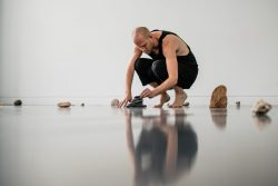 Artist Luke Pell crouches on shiny floor with natural objects surrounding him