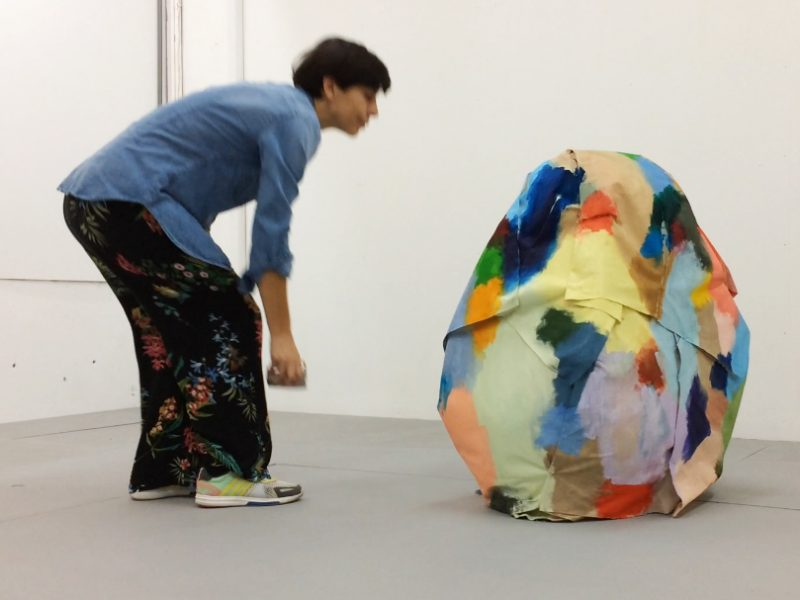 Artist Isabel Cordeiro leans over an egg shaped sculpture that is covered in brightly painted fabric