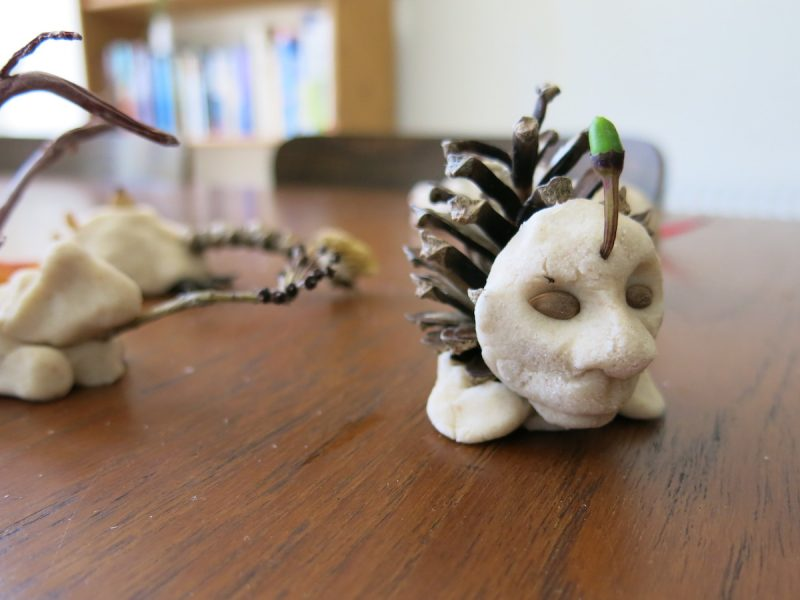 A creature made from a pine cone, a face made from salt dough and seeds for eyes placed on a wooden table
