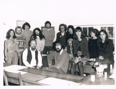 black and white photo from the 1970s of a group of 9 men and 4 women stood around and sat on tables.