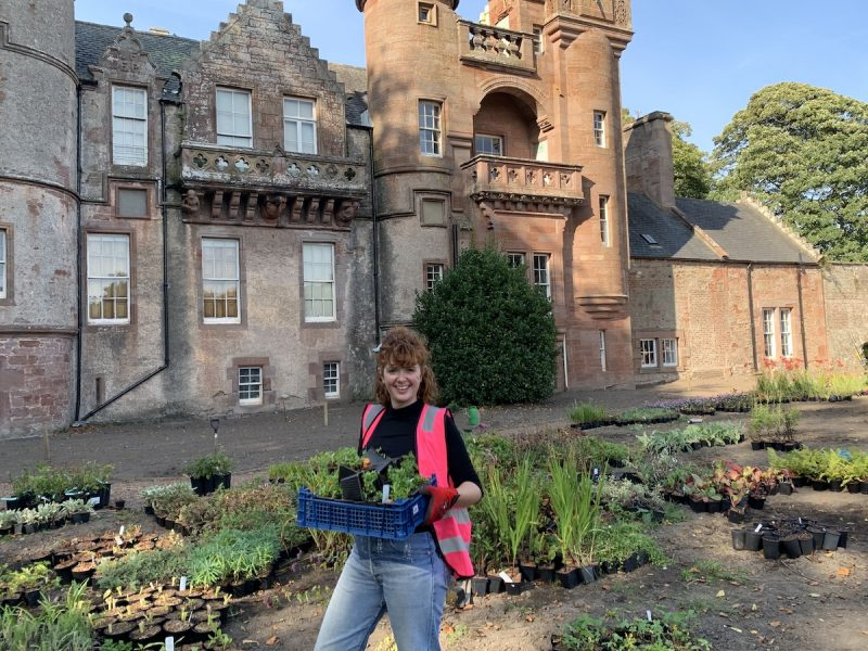Kirsten Wilson Engagement Manager Smiles at the camera while holding pots of plants