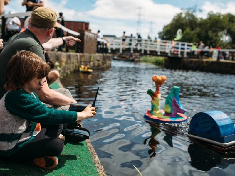adult man and child leaning into canal with floating sculpture