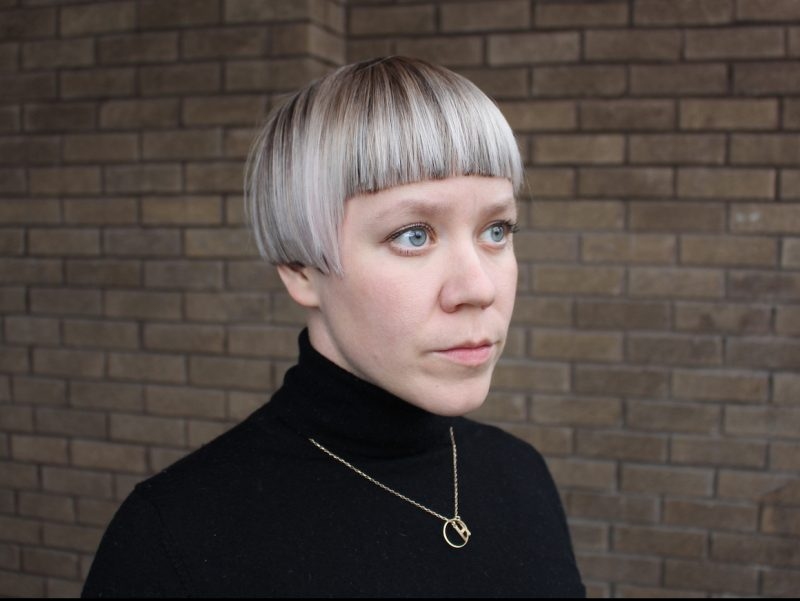 a photograph portrait of the artist Hanna stands in front of a brick wall, looking past the camera.