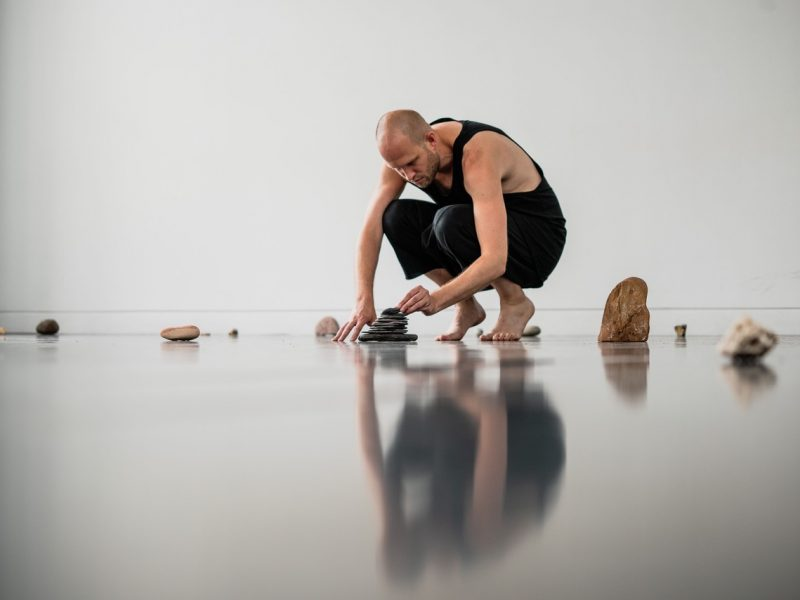 a photograph of a crouching figuring, the artist Luke Pell, drawing on the ground