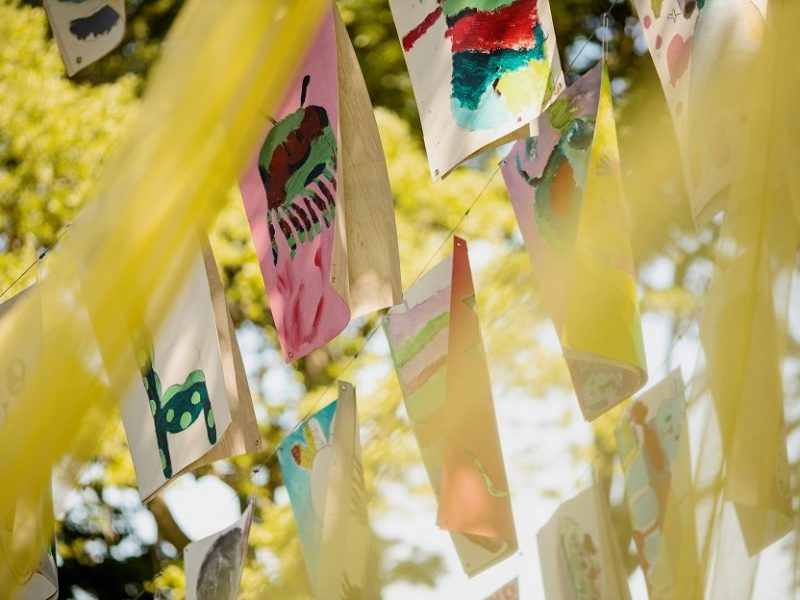 Childrens painting hang like banner from trees