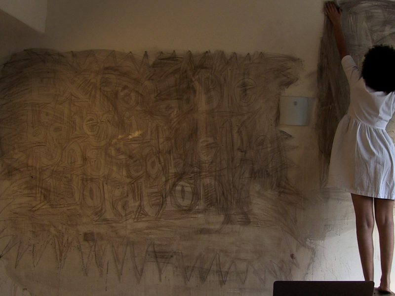photo of artist Jade Montserrat stood with her back to the camera. She is wiping charcoal off a wall
