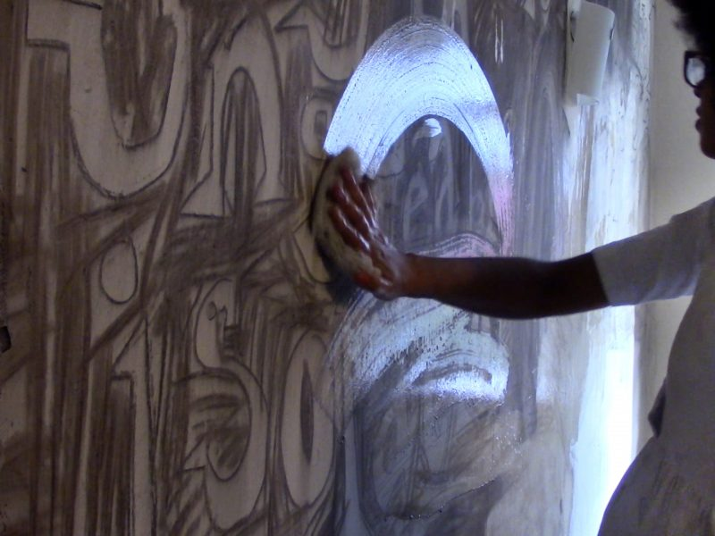 Photo of artist Jade Montserrat arm and hand as she is wiping charcoal off a wall