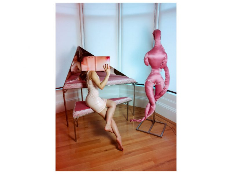 Image of a femme figure with a pink silk mannequin