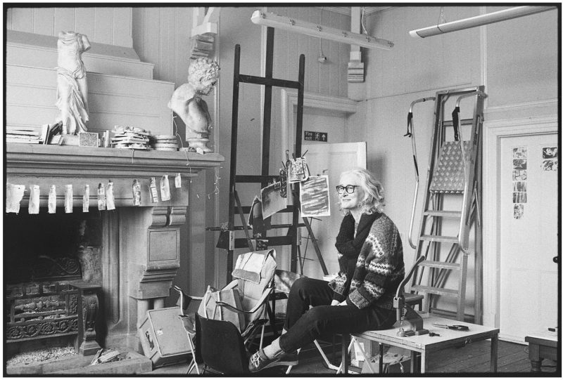 Image of a woman sitting in a painting studio