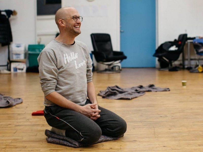 Artist Luke Pell sitting ona wooden floor on knees smiling