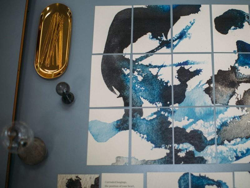 Ink drawings in blue and black on paper with stationery beside it
