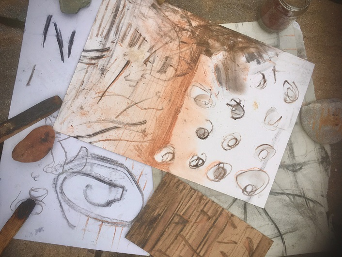 Papers with shapes and lines drawn in chalk in red and brown colours