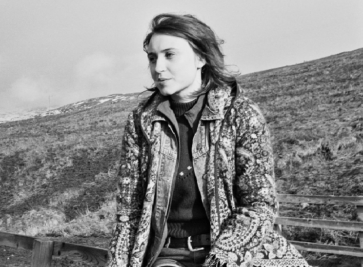 Black and white picture of artist rachael bibby on a hillside