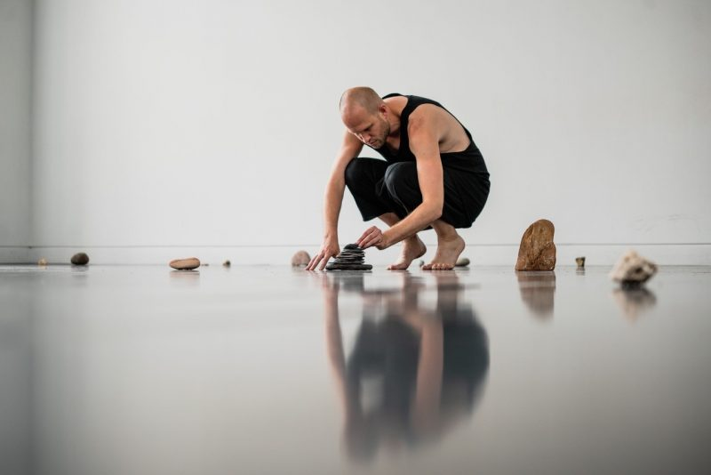 Man wearing black crouches down on a shiny floor surrounded by object that look like pebbles