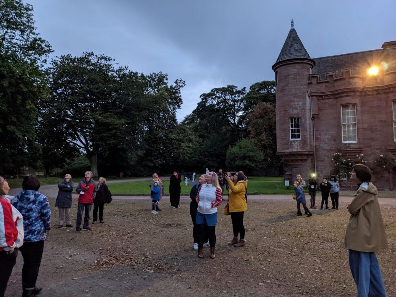 A group of people standing outside looking at a darkening sky